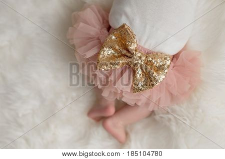 A close up image of a large gold sequin bow located on the frilly bloomers of a baby girl's bottom.