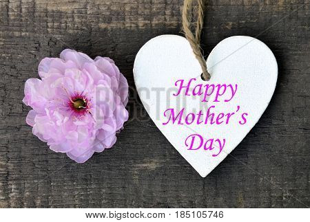 Happy Mother's Day.Pink Sakura flower and decorative wooden heart on old wooden background.Mother's Day greeting card.Selective focus.