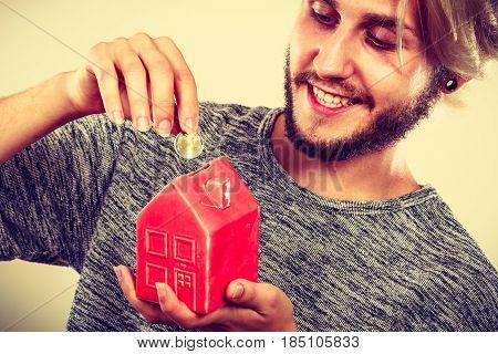 Smiling Man Putting Coin Into House Piggybank