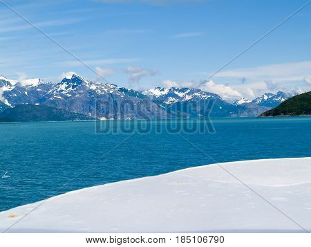 Turquoise water of Alaskan fjord between stark white snow foreground and grey mountains and blue sky