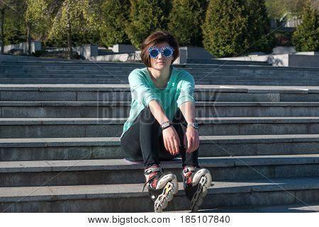 Tired Young Woman In Funny Sunglasses Sits On The Steps In The Park
