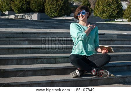 Joyful Young Woman Sits On The Steps In The Park And Measures Her Pulse