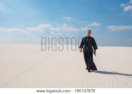Resolute Man With Sword In Traditional Japanese Clothes Goes Along Desert