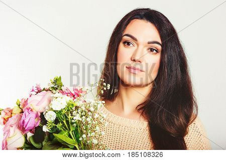 Close up portrait of 35-40 year old woman with black hair, holding big bouquet of spring flowers, standing against white background