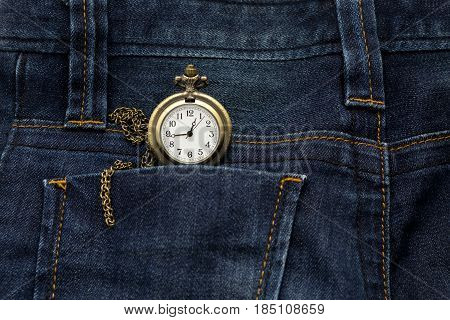 gold pocket watch in back pocket blue jean pants this image for fashion and vintage