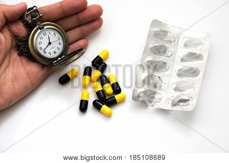 Heap Of Medicine Capsule, Empty Medicine Pack And  Hand Of Woman Holding Pocket Watch Put On White B