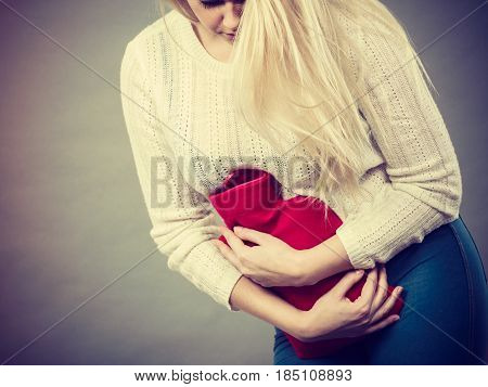 Woman Feeling Stomach Cramps Holding Hot Water Bottle