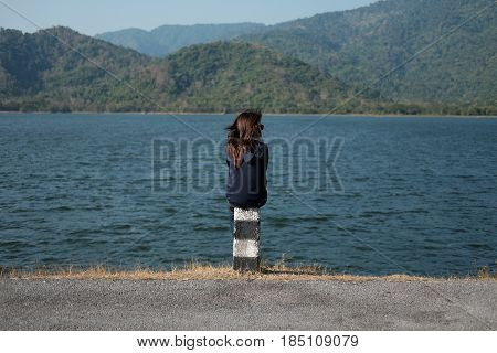 Woman Sitting On Pillar Roadside Front Of Her Have Big Lake And Mountain Background. This Image For