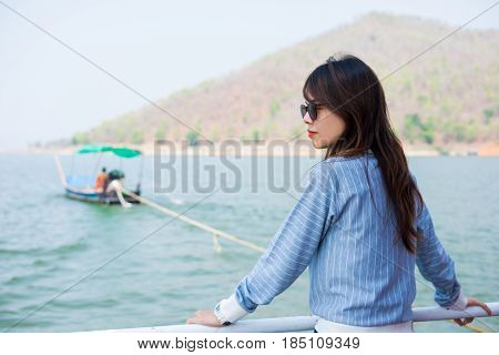 Young Woman Lone Moment Standing Viewing Scenery On Boat. Front Of Her Have Lake And Mountain Are Ba
