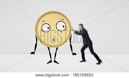 A businessman trying to push a golden coin with arms, legs and a face on white background. Business and profit. Earnings. Smart investment.