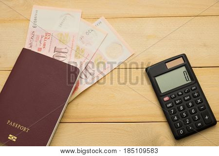 Top View. Singapore Dollar Cash Middle Insert On Passport Book And Have Calculator Putting On Wooden