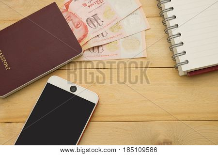 Top View. Singapore Dollar Cash Middle Insert On Passport Book And Have Smartphone And Empty Noteboo