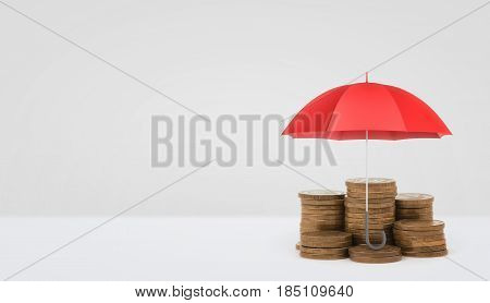 A red open umbrella vertically placed over several stacks of golden coins on white background. Safe banking and deposits. Investment insurance. Saving money for future.