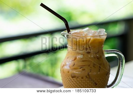 Iced Coffee In Glass Pitcher Putting On Table. Have Blurred Nature Background. This Image For Food A