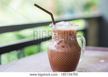 Iced Cocoa In Glass Pitcher Putting On Table. Have Blurred Nature Background. This Image For Food An