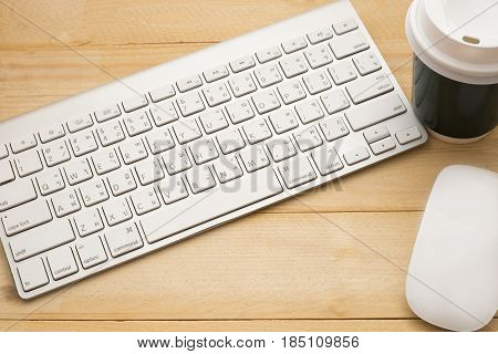 Top View. Computer Equipment. Keyboard,  Mouse And Plastic Coffee Glass Putting On Wooden Background
