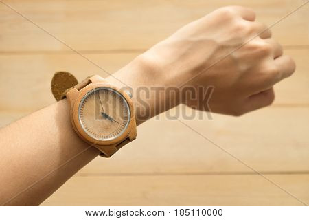 Top View. Young Woman Equip Wooden Wrist Watch On Her Arm Have Wooden Are Background. This Image For