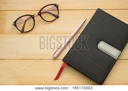 Top View. Glasses, Pen And Black Cover Notebook Putting On Wooden Are Background. This Image For Edu