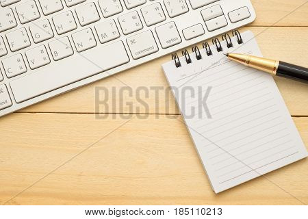 Top View. Keyboard,pen And Small Empty Notebook Paper. Both Putting On Wooden Are Background. This I