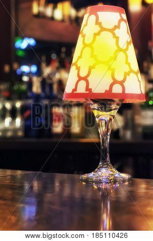 A light fixture sitting on a bar.