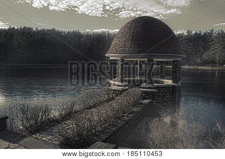 A sepia photograph of a gazebo in the woods on a lake during winter time.