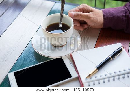 Top View. Arm Of Businessman,coffee Cup With Coffee,mobile Phone And Pen Putting On Top Notebook Pap