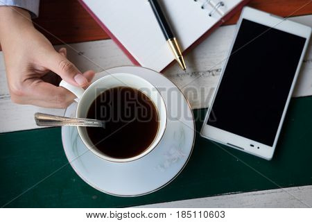 Top View. Hand Of Businessman Holding Coffee Cup With Coffee And Have Mobile Phone, Pen Put On Top E