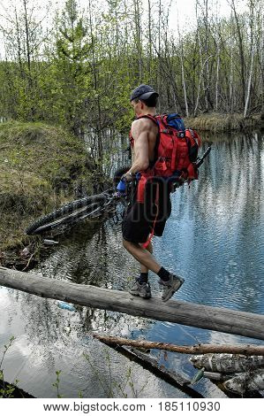 Cycle Tourist Passes A Water Barrier On A Log