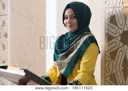 Young Muslim Woman Reading The Koran