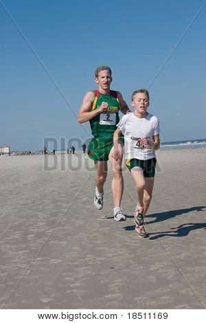 JACKSONVILLE, FLORIDA - FEBRUARY 14: Runners Shawn Williams, age 34 of Jacksonville & Eddy Pfeil, age 14 of Lockport, NY, compete in the Winter Beach Run on February 14, 2010 in Jacksonville, Florida.