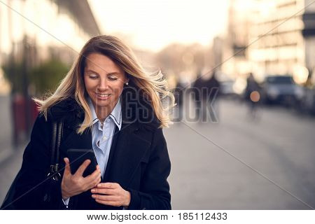 Fashionable middle-aged Woman in Black Coat and blond hair Busy with her Mobile Phone While Walking a City Street