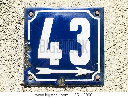 Weathered grunge square metal enameled plate of number of street address with number 43 closeup
