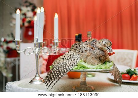 a wounded pheasant hunting. cooked chef to the Banquet. Traditional still life feast.