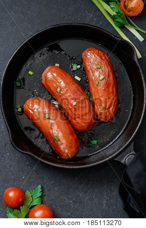 Top view on fried sausages in a black frying pan on a black table with tomatoes and greens.