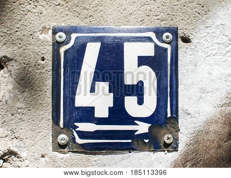 Weathered grunge square metal enameled plate of number of street address with number 45 closeup