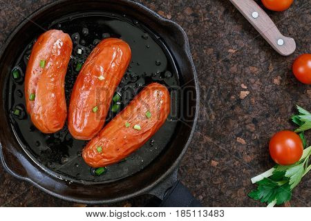Top view on fried sausages in a black frying pan on a brown table with tomatoes and greens.