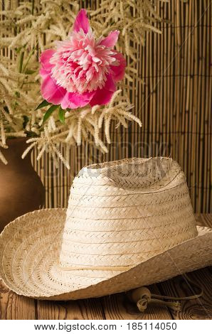 Straw hat and peony flower, close up