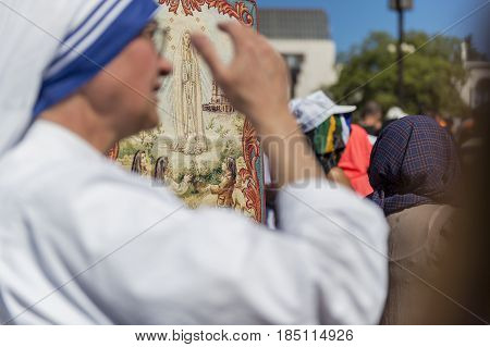 Fatima Portugal - May 13 2014: Blurred silhouette of a nun with the figure of the Virgin Mary on the background at the Sanctuary of Fatima during the celebrations of the apparition of the Virgin Mary in Fatima Portugal.