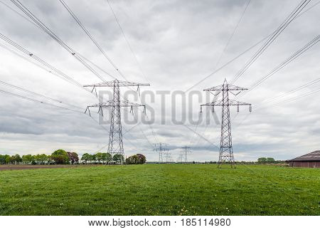 Converging high voltage cables and steel pylons in an agricultural Dutch landscape at a cloudy day in the spring season.