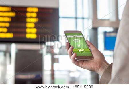 Airport wifi. Free wireless internet connection in terminal. Woman browsing web and going online before departure. Hand holding mobile phone. Timetable and schedule in the blurred background.