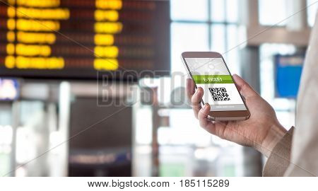 Buying online ticket from internet. E-ticket on mobile phone screen with schedule in the blurred background. Universal public transportation terminal. Bus, train, metro, subway or underground station