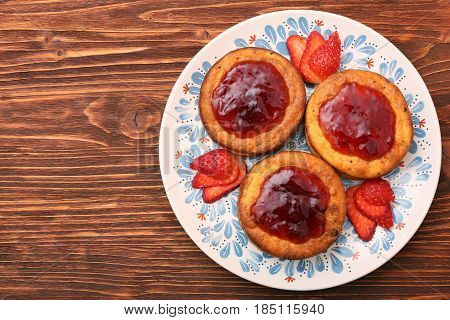 Cottage cheese patties with strawberry jam on wooden background.
