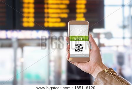 E-ticket on smartphone screen with timetable in the blurred background. Buying online ticket from internet. Universal public transportation terminal. Bus, train, metro, subway or underground station
