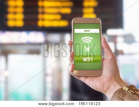 Airport wifi. Free wireless internet connection in terminal. Browsing web and going online before flight. Woman holding smart phone in hand. Timetable and schedule in the blurred background.