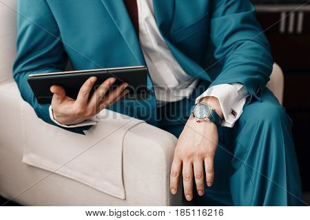 Businessman keep a digital tablet in hand whilst sitting on a sofa in a blue suit. on hand expensive mechanical watch with leather strap. shirt with cufflinks.