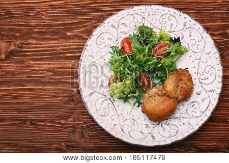 Smoked chicken leg with salad on wooden table. Healthy low fat eating concept.