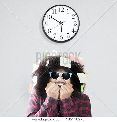 Afraid man biting nail with wall clock and sticky notes over his head isolated on white background