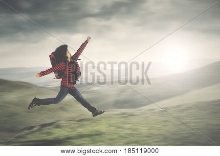 Picture of Afro male carrying a backpack while running in the mountain with fast motion blur background