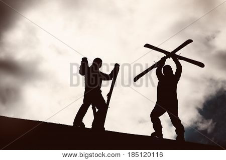 Skier stands mountain top with ski in hands on sunset backdrop. Silhouette. Skiing and sports concept. Bigwood Kirovsk ski resort.