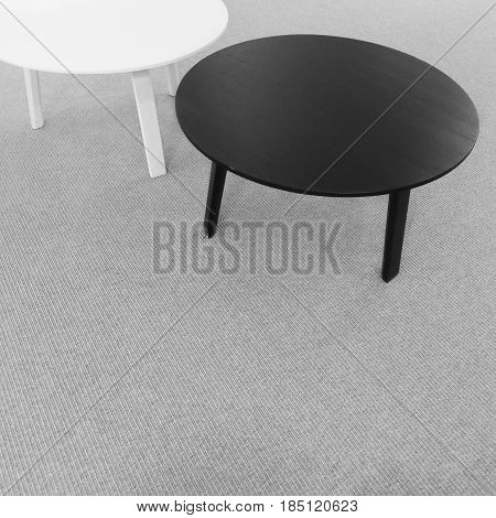 Round black and white tables on carpet floor. Modern furniture.